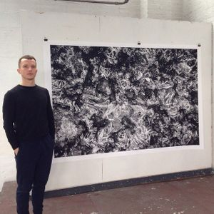 Maciej Urbanek infront of his work