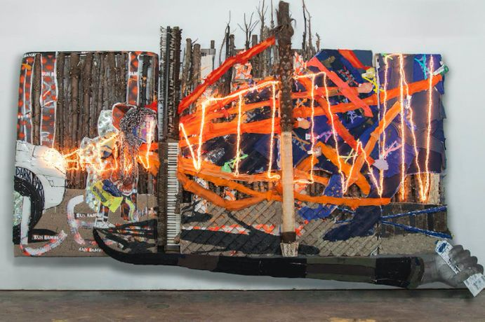 Aaron Fowler, Lex Brown Town, 2017. Christmas tree trunks, fake palm tree, pianos, shirtsleeves, shirts, acrylic and enamel paint, paint tubes, dirt, tire, car parts, hair weave, Minions backpack, graduation cap, CDs, LED rope lights, and Plexiglas on wood panels and truck topper, 16 × 12 × 3 ft (4.9 × 3.7 × 1 m). Courtesy the artist