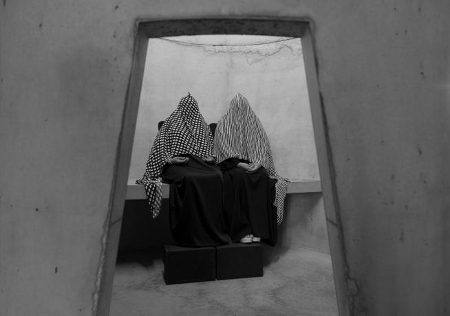 Two Venezuelan mourners, Ana Luisa Montiel De Fernandez and Marisol Rosalia Montiel Fernandez, wearing long patterned head coverings in the concrete structures erected as part of Taryn Simon's An Occupation of Loss. The piece was performed at the Park Avenue Armory in New York in 2016.