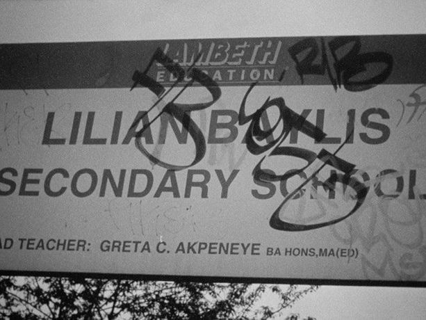 "Image ID: A black and white photo of a secondary school sign that has been graffitied with thick, stylised writing. You can still read ""Lambeth Education. Lilian Baylis. Secondary School. Teacher: Greta C. Akpeneye BA HONS, MA (ED)"" under the graffiti."