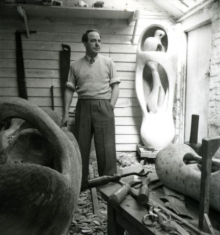 Henry Moore in his studio Perry Green c. 1953-54, with working model plasters for Upright Internal External Form (r.) and the elmwood carving in progress (l.) © The Henry Moore Foundation. All Rights Reserved, DACS 2015 / www.henry-moore.org.