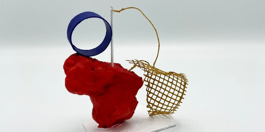 A small mixed media sculpture on a white background. Appears to be made from card, foam and mesh. Parts of it are painted primary colours: red, blue and yellow.