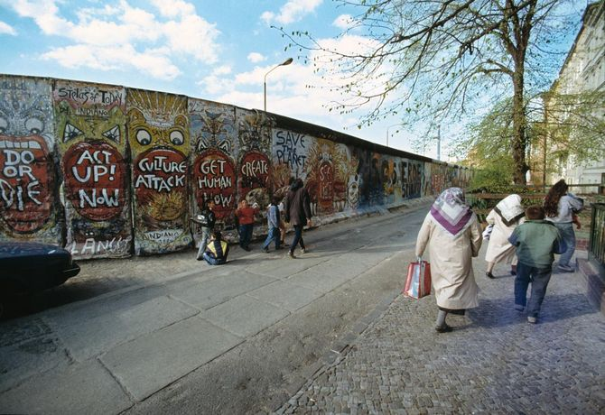 Turkish Berlin women and children on Leuschnerdamm in Berlin-Kreuzberg. In the background, the Berlin Wall spray-painted by graffiti artist Indiano, 1989/90 © Stadtmuseum Berlin | photo: Ergun Cağatay