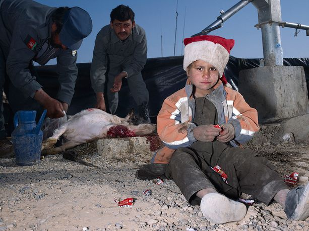 Mark Neville, 'Child, Jacket, Slaughtered Goat, Sweets, Painted Nails, Xmas Day, Helmand', 2010, courtesy Mark Neville