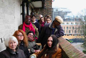 Resident workshop on the balcony of Samuel House, Haggerston discussing the history of public housing in London. (Credit: Fugitive Images)