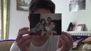 filmpro lates August 2015: Johnny Hourigan and Clare Bottomley  Everyobody Says It's All in Your Head. Still image. Description: Johnny holds a photo of his family in front of him, covering his face. Photo Credit: Clare Bottomley