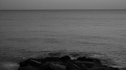 Fleches Sans Corps (Arrows without Bodies), filmpro lates, Thursday 2 July 2015. Still image titled 'Nocturnal Impasse'. Photo description: A black and white view of the smooth sea from the shore. Photo Credit: Juan delGado