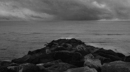 Fleches Sans Corps (Arrows without Bodies), filmpro lates, Thursday 2 July 2015. Still image titled 'Monring Impasse'. Photo description: A black and white view of the sea over a rocky shore, white clouds in the sky. Photo Credit: Juan delGado