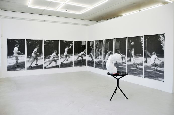Front: Victor Santamarina, Fantasía, 2019, white concrete and fake leather red glove, Back: Ilke Gers, Marcel, 2019, Digital print on paper, Installation 160 x 1032 cm, (160 x 84 cm each)