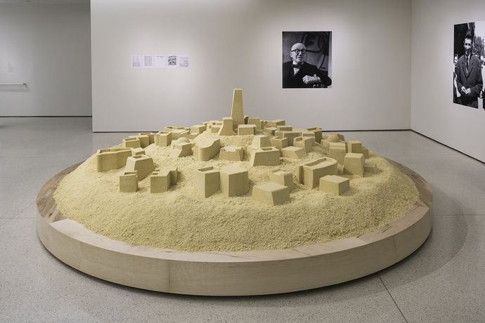 Kader Attia, Untitled (Ghardaïa), 2009/2017, installation view, But a Storm Is Blowing from Paradise: Contemporary Art of the Middle East and North Africa, Solomon R. Guggenheim Museum, New York, 2016, cooked couscous on plinth, digital prints on paper, Solomon R. Guggenheim Museum Collection, New York, image courtesy the artist, Galerie Nagel Draxler, Berlin/Cologne and Lehmann Maupin, New York and Hong Kong © the artist