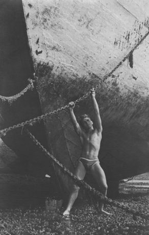 Male bather pulling on anchor chain, 1930s