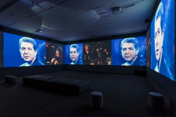 George Fok, Passing Through, 2017. Multi-channel video installation, black and white and colour, sound, 56 min 15 s, looped. Projection on three walls, dimensions variable. Commissioned by the Musée d'art contemporain de Montréal. Exhibition view of Leonard Cohen: A Crack in Everything presented at the Musée d'art contemporain de Montréal from November 9, 2017 to April 12, 2018. Courtesy the artist. Photo: Richard-Max Tremblay