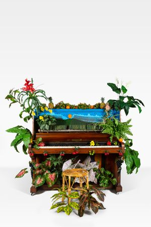 Benjamin Patterson, Piano d'oiseaux tropical, 1989. Piano, bamboo stool, artificial plants and fruits, oil paint. 185 x 260 x 115 cm. Courtesy of the Archivio Conz.