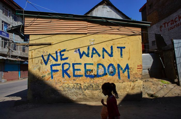 A Kashmiri girl walks past graffiti reading, 'We want freedom' during a curfew and shutdown in downtown Srinagar on September 7, 2016.