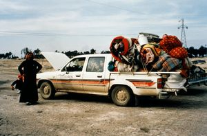 A family and their overloaded car at a refugee centre on the Iraq-Kuwait border, during the First Gulf War, 1991. © John Keane (IWM GLF 174)