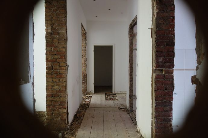 View into a gutted apartment through the keyhole.