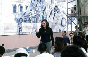 "Judith F. Baca, Photograph of The Great Wall of Los Angeles A view of Judy Baca and mural-makers meeting at the 1940's section titled ""David Gonzalez"" in progress. Photograph courtesy of SPARC Archive. ©1976 Judith F. Baca"