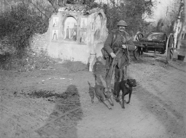 Ernest Brooks, Soldier from the Royal Engineers with two messenger dogs and a roadside shrine, December 1917, Imperial War Museum