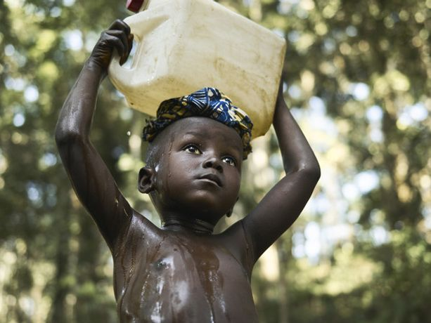 Four-year-old Ibrahim carries a container of dirty water on his head on his way home from the stream in the forest near Tombohuaun, Sierra Leone. WaterAid/ Joey Lawrence