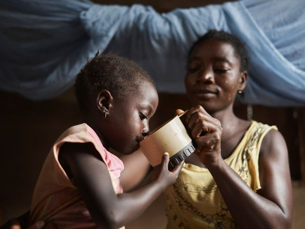 Fatu gives a drink of dirty water to her daughter Nancy, 6, at home in Tombohuaun. WaterAid/ Joey Lawrence