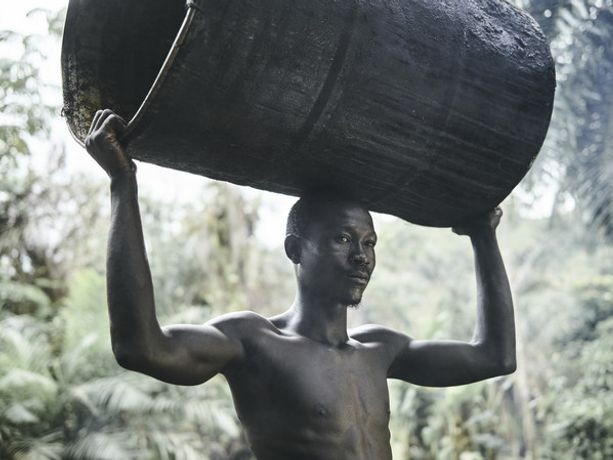 Aruna, 24, carries a barrel at one of the several palm plantations in Tombohuaun. WaterAid/ Joey Lawrence.