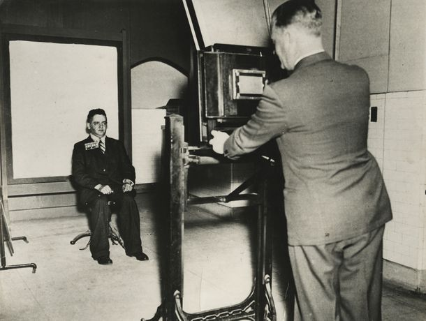 Weegee, Weegee getting a mug shot at station house, New York, c.1936