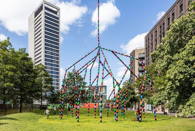 Eva Rothschild's sculpture, My World And Your World, situated on green grass. The sculpture has multi-coloured and black stripes and spindly arms propping it up, like a spider or a rake. The sculpture has one pole that reaches out of frame from the image,