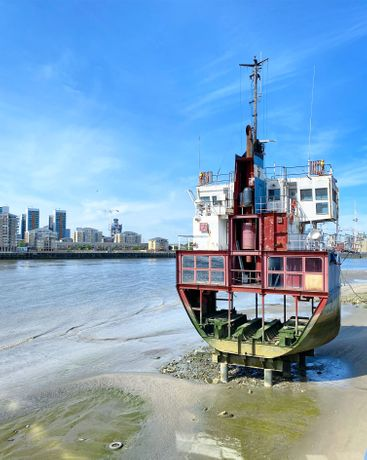 Richard Wilson's A Slice of Reality at Greenwich Peninsula, a slice of a cross-section of a ship, situated on a mossy beach against a blue sky with buildings in the background across the water.