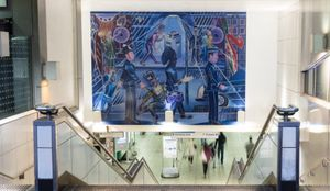 Denzil Forrester's painting Brixton Blue, a stylistic imagery showing figures on the street including police officers, pedestrians and merchants, hanging above an escalator to the London Underground.